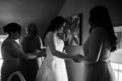 bridesmaid-holding-brides-hand-while-getting-in-dress