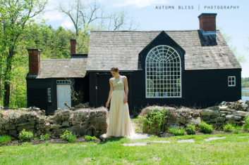 woman-standing-by-rock-wall-near-historic-house