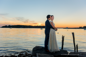 Newlyweds Share a Kiss By the Water at Sunset