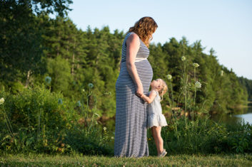 little-girl-looking-up-at-pregnant-mom-maine-family-documentary-photographer