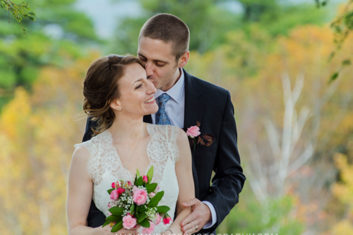groom-kissing-bride-in-maine-fall-foliage